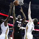 Miami Heat forward Udonis Haslem (40) shoots against New Orleans Pelicans forward Tyreke Evans, left, and New Orleans Pelicans forward Luke Babbitt, right, during the first half of an NBA basketball game in New Orleans, Saturday, March 22, 2014 The Associ