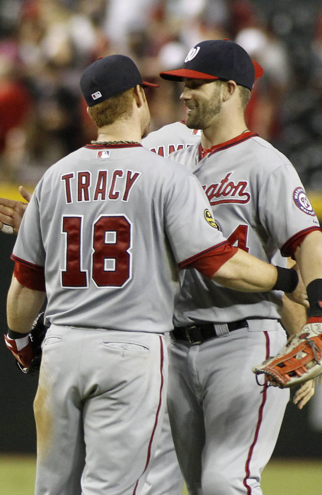 Washington Nationals' Chad Tracy (18) is embraced by teammate Bryce Harper after a 2-0 victory over the Arizona Diamondbacks in a baseball game on Saturday, Sept. 28, 2013, in Phoenix. Tracy hit a solo home run during the seventh inning in the victory