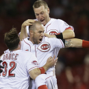 Cincinnati Reds' Skip Schumaker, center, celebrates with Jay Bruce (32) and Todd Frazier, top, after hitting a double to drive home Marlon Byrd for the game-winning run in the ninth inning of a baseball game against the Colorado Rockies, Tuesday, May 26, 2015, in Cincinnati. The Reds won 2-1. (AP Photo/John Minchillo)
