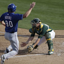 Oakland Athletics catcher Chris Gimenez, right, waits for the throw before tagging out Texas Rangers' Jared Hoying during the seventh inning of a spring training baseball game Saturday, March 1, 2014, in Phoenix The Associated Press
