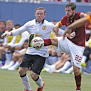 Manchester United's Wayne Rooney, left, and AS Roma's Mattia Destro fight for control of the ball during an exhibition soccer match at Mile High Stadium in Denver, Saturday, July 26, 2014. Manchester United won 3-2