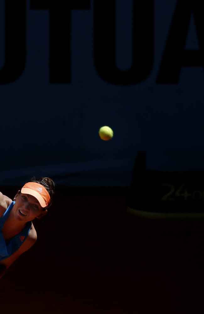 Simona Halep from Romania serves the ball during a Madrid Open tennis tournament match against Ana Ivanovic from Serbia in Madrid, Spain, Friday, May 9, 2014