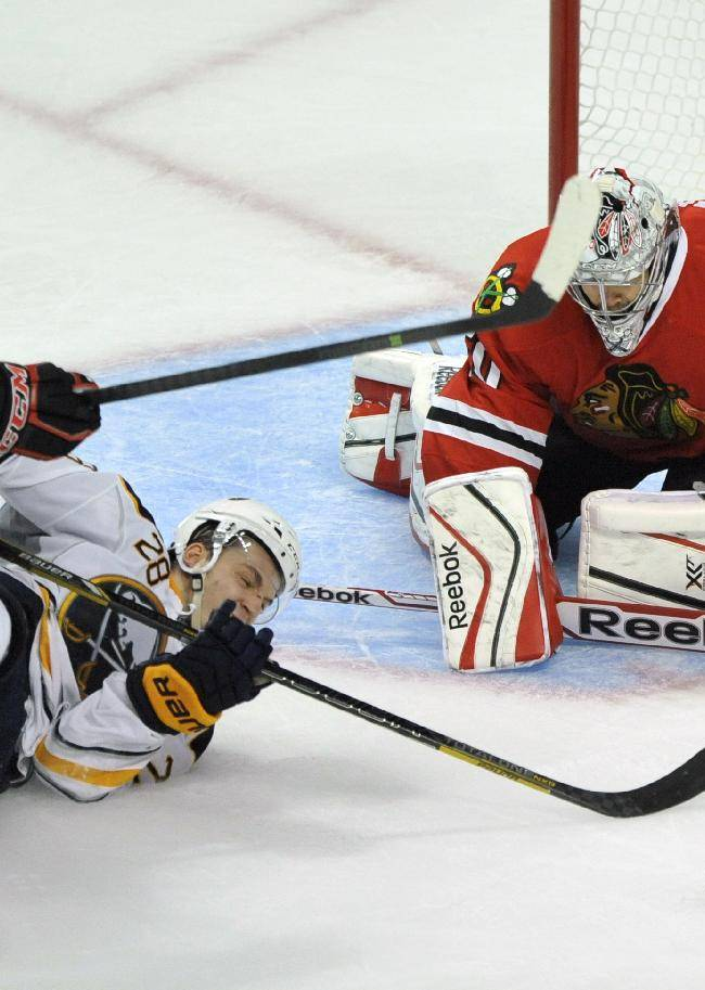 Buffalo Sabres' Zemgus Girgensons (28), of Latvia, battles Chicago Blackhawks' Sheldon Brookbank (17), for the puck while Chicago Blackhawks goalie Corey Crawford defends the goal during the third period of an NHL hockey game in Chicago, Saturday, Oct. 12, 2013. Chicago won 2-1