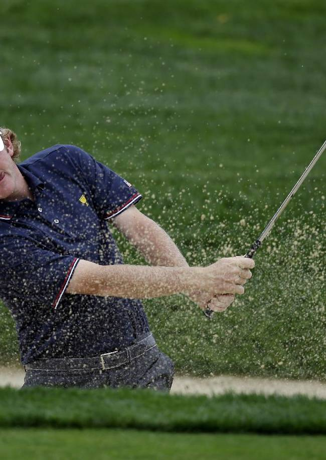 United States team player Brandt Snedeker hits out of a bunker on the first hole during the four-ball match at the Presidents Cup golf tournament at Muirfield Village Golf Club Thursday, Oct. 3, 2013, in Dublin, Ohio