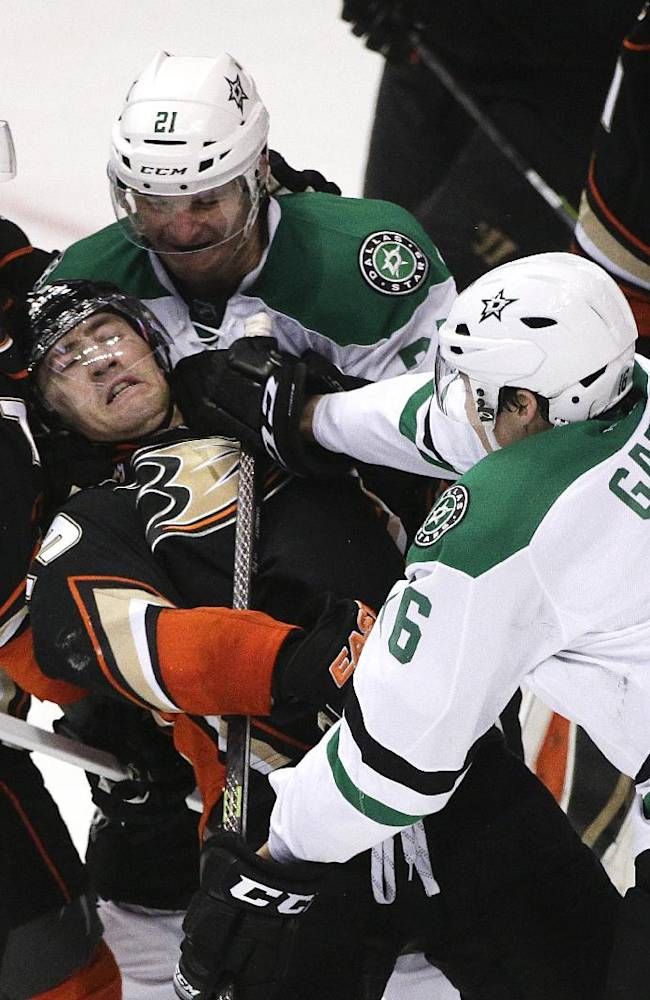 Anaheim Ducks' Stephane Robidas, center, is shoved by Dallas Stars' Ryan Garbutt, right, during the second period in Game 1 of the first-round NHL hockey Stanley Cup playoff series on Wednesday, April 16, 2014, in Anaheim, Calif