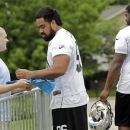 THIS CORRECTS THE FIRST NAME TO KAWANN, NOT KAWAAN AS ORIGINALLY SENT -  Carolina Panthers' first-round draft pick, defensive tackle Star Lotulelei (96) signs an autographs as the team's second round pick, Kawann Short (68), walks past during NFL football practice in Charlotte, N.C., Thursday, May 23,2013. (AP Photo/Bob Leverone)