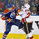 Calgary Flames' Lee Stempniak (22) checks Edmonton Oilers' Andrew Ference (21) during second period NHL hockey action in Edmonton, Alberta., on Saturday Dec. 7, 2013 The Associated Press