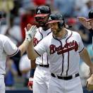 In this photo taken Wednesday, May 22, 2013, Atlanta Braves' Evan Gattis, second from right, is greeted by teammates from left, Chris Johnson, Jason Heyward, and Freddie Freeman after hitting a grand slam in the fourth inning of a baseball game against the Minnesota Twins in Atlanta.  It's hard not to get caught up in this modern-day tale, a guy who quit baseball for nearly four years, yet found his way back. Gattis made the Braves as a non-roster player, and has become a downright sensation as a 26-year-old rookie. (AP Photo/David Goldman)