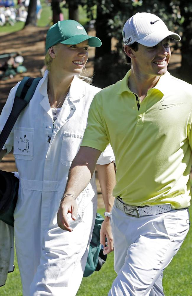 Rory McIlroy, of Northern Ireland, walks with tennis player Caroline Wozniacki during the par three competition before the Masters golf tournament Wednesday, April 10, 2013, in Augusta, Ga