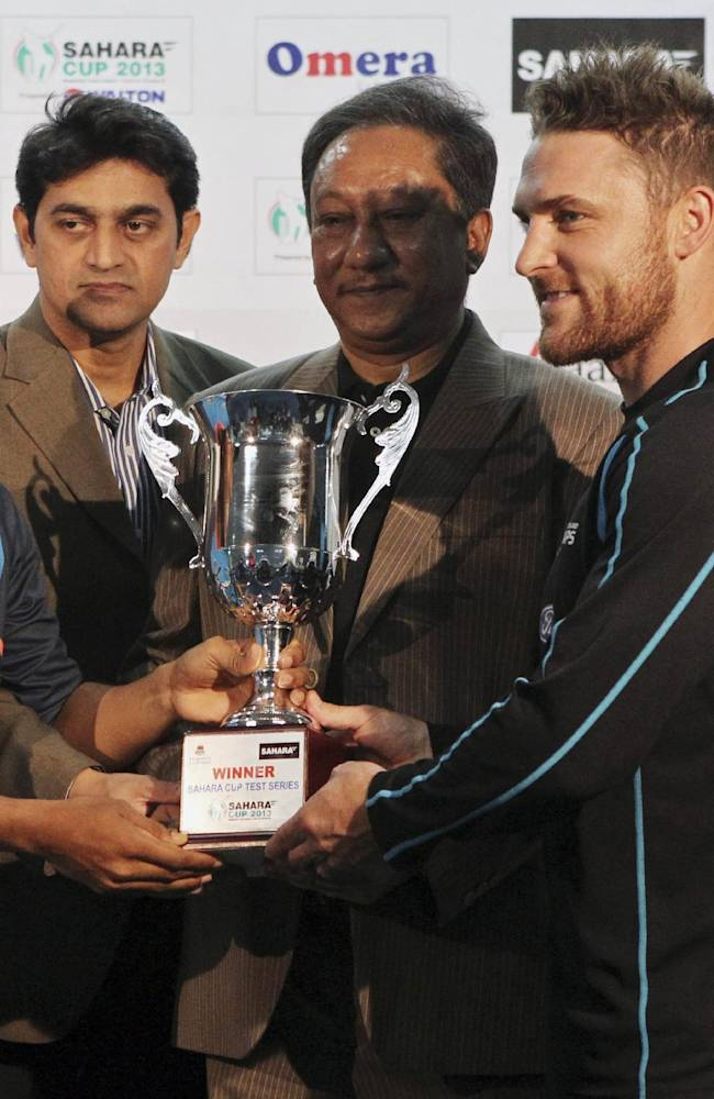Bangladesh's captain Mushfiqur Rahim, left, and New Zealand's captain Brendon McCullum, right, take the tournament trophy from Bangladesh Cricket Board (BCB) President Nazmul Hasan Papon, center, during a presentation ceremony after the second test cricket match between them in Dhaka, Bangladesh, Friday, Oct. 25, 2013. The match ended in a draw on the fifth and the final day Friday
