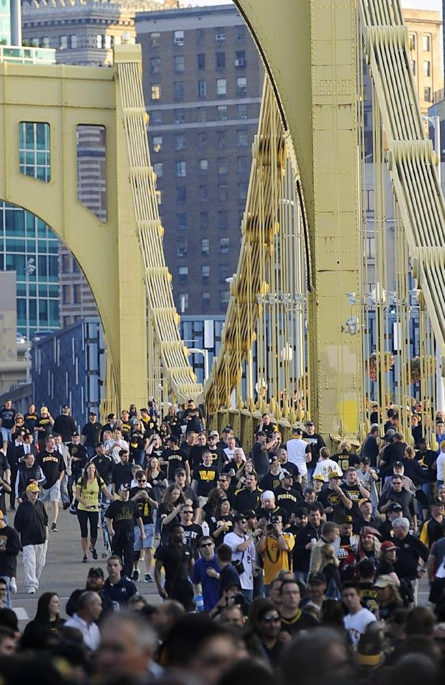 People cross the Roberto Clemente Bridge on their way to the NL wild-card playoff baseball game between the Pittsburgh Pirates and the Cincinnati Reds on Tuesday, Oct. 1, 2013, in Pittsburgh. The Pirates were making their first post-season appearance since 1992