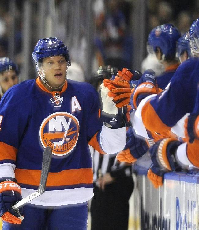 New York Islanders' Kyle Okposo (21) is congratulated by teammates after scoring against the Buffalo Sabres in the first period of an NHL hockey game on Saturday, March 15, 2014, in Uniondale, N.Y