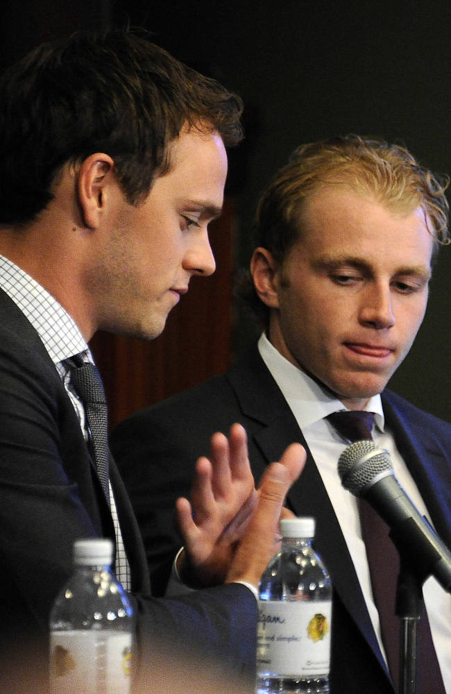 Chicago Blackhawks players Jonathan Toews, left, and Patrick Kane listen to the media during a news conference at the United Center in Chicago, Wednesday, July 16, 2014. The Blackhawks recently agreed to eight-year contract extensions with for their star players