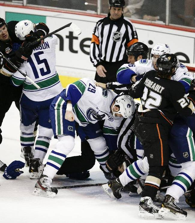 The Anaheim Ducks and the Vancouver Canucks players engage in a fight during the third period of an NHL hockey game on Wednesday, Jan. 15, 2014, in Anaheim, Calif. The Ducks won 9-1