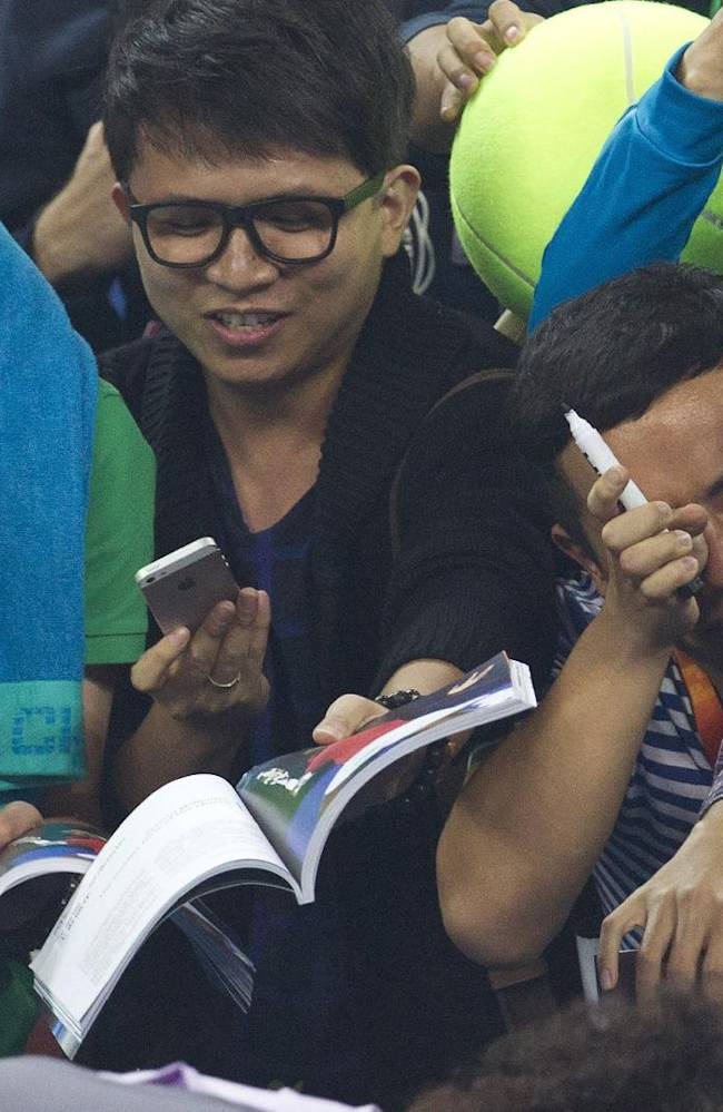 A Chinese fan, right, weeps after he received autographs from Serena Williams of U.S. after the quarterfinal match of the China Open tennis tournament at the National Tennis Stadium in Beijing, China Friday, Oct. 4, 2013. Williams beat Wozniacki 6-1, 6-4