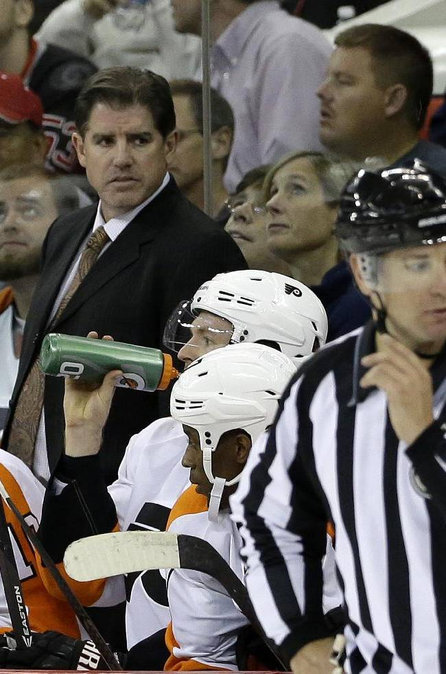 In this Sunday, Oct. 6, 2013 photo Philadelphia Flyers coach Peter Laviolette watches from the bench during the first period of an NHL hockey game against the Carolina Hurricanes in Raleigh, N.C. The Flyers fired coach Laviolette, a person familiar with the decision told The Associated Press on Monday, Oct. 7, 2013