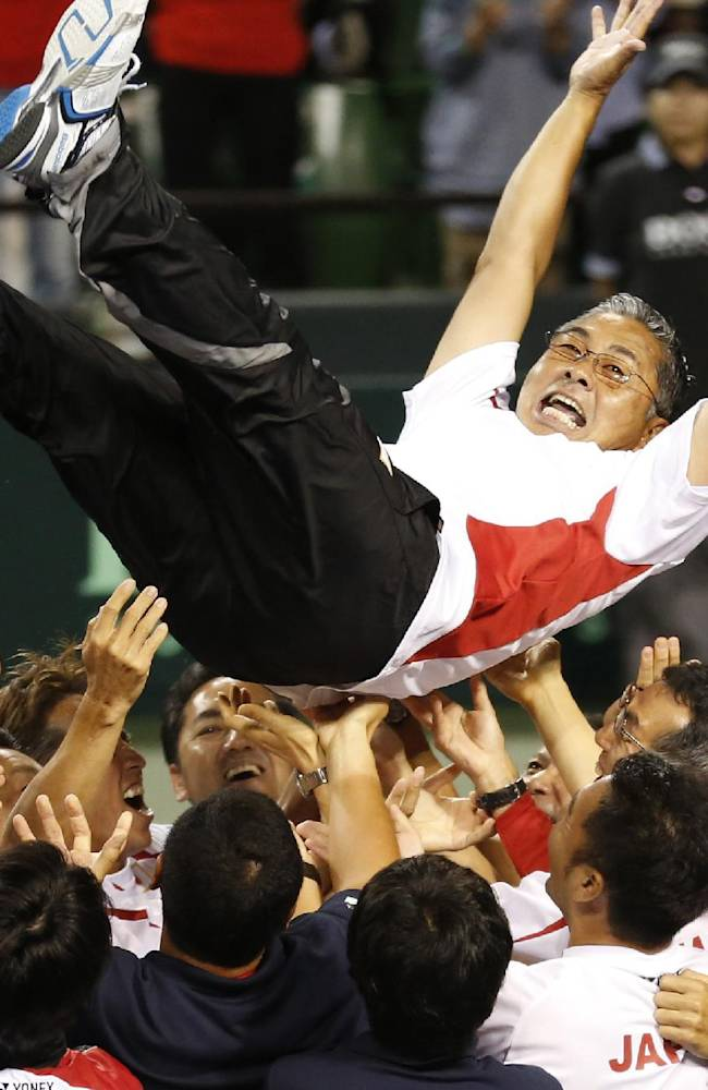 Japan's team members toss Team Captain Minoru Ueda into air after the team won the Davis cup world group play off against Colombia in Tokyo, Sunday, Sept. 15, 2013