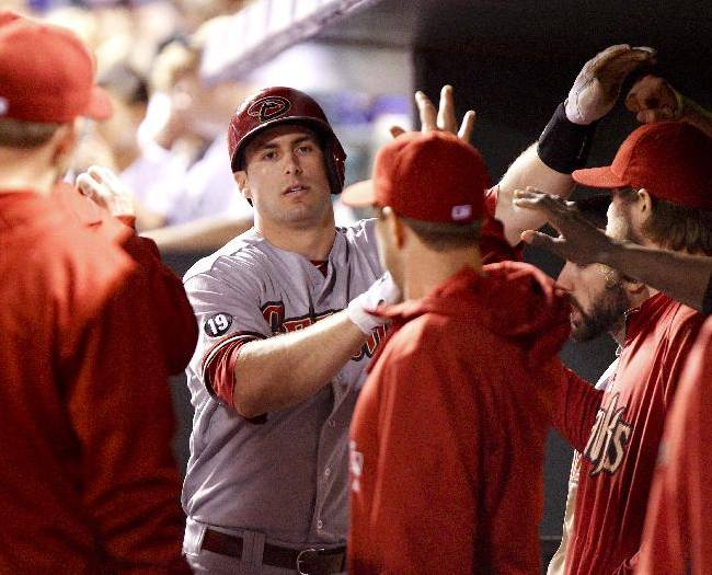 Arizona Diamondbacks' Paul Goldschmidt is congratulated by teammates after hitting his NL leading 35th home run of the year during the seventh inning of a baseball game against the Colorado Rockies, Friday, Sept. 20, 2013, in Denver