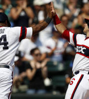 Chicago White Sox's Dayan Viciedo and Josh Phegley celebrate after scoring during the third inning of a baseball game against the Texas Rangers, Sunday, Aug. 25, 2013, in Chicago. (AP Photo/Andrew A. Nelles)