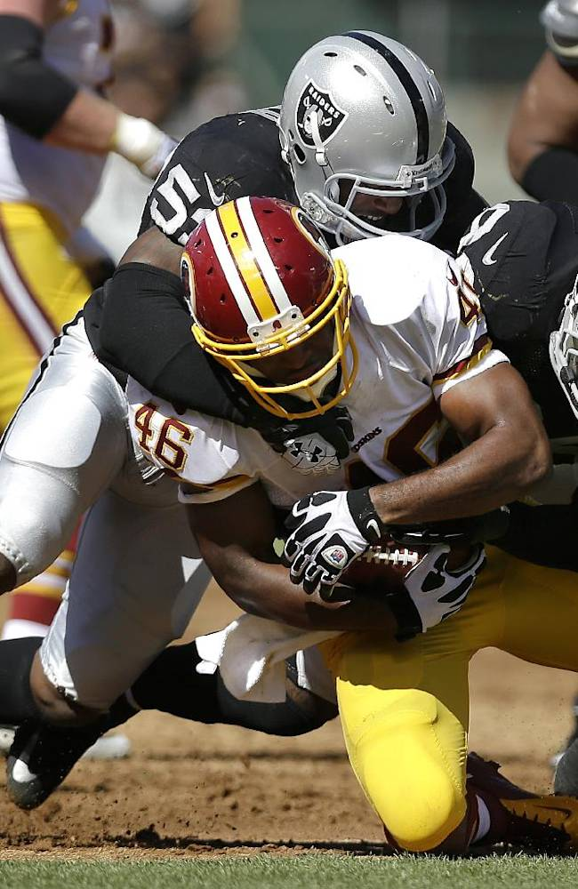 Washington Redskins running back Alfred Morris (46) is tackled by Oakland Raiders linebacker Nick Roach, top, and outside linebacker Kevin Burnett during the first half of an NFL football game in Oakland, Calif., Sunday, Sept. 29, 2013