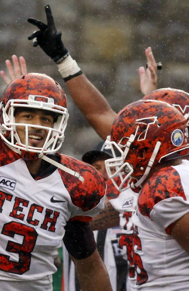 In this Sept. 21, 2013, file photo, Virginia Tech quarterback Logan Thomas (3) celebrates scoring the winning touchdown after a third overtime of an NCAA college football game against Marshall in Blacksburg, Va. College football is well into the patriotic era first evoked by the camouflage uniforms that debuted in the Army-Navy game five years ago