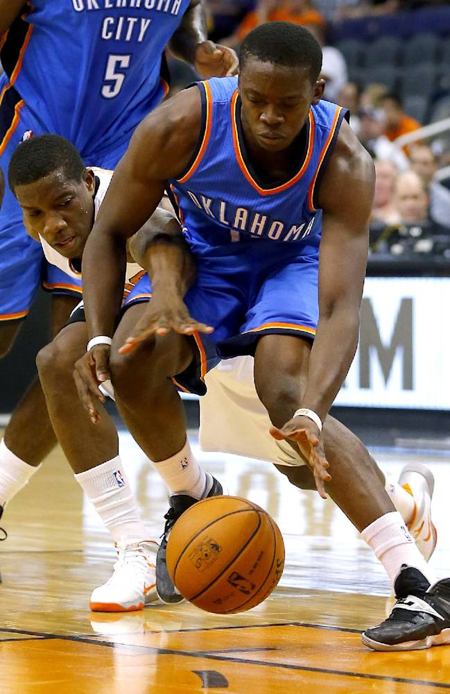 Phoenix Suns' Eric Bledsoe, rear, fouls Oklahoma Thunder guard Reggie Jackson during the first half of an NBA preseason basketball game, Tuesday, Oct. 22, 2013, in Phoenix
