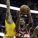 Washington Wizards' Nene Hilario (42), from Brazil, goes up to shoot against Cleveland Cavaliers' Tristan Thompson in the first quarter of an NBA basketball game on Wednesday, Nov. 20, 2013, in Cleveland The Associated Press