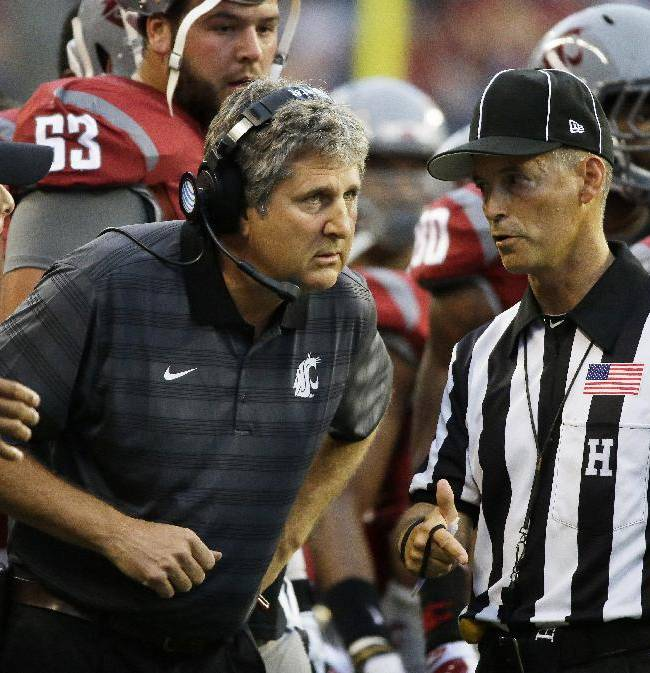 Washington State coach Mike Leach, center, talks with an official during the first half of an NCAA college football game against Rutgers, Thursday, Aug. 28, 2014, in Seattle