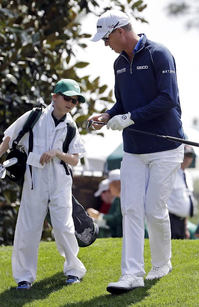 John Senden, of Australia, walks with his son Jacob during the par three competition at the Masters golf tournament Wednesday, April 9, 2014, in Augusta, Ga