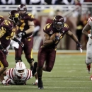 Central Michigan running back Zurlon Tipton (34) breaks away from the Western Kentucky defense during the second quarter of the Little Caesars Pizza Bowl NCAA college football game at Ford Field in Detroit, Wednesday, Dec. 26, 2012. (AP Photo/Carlos Osorio)