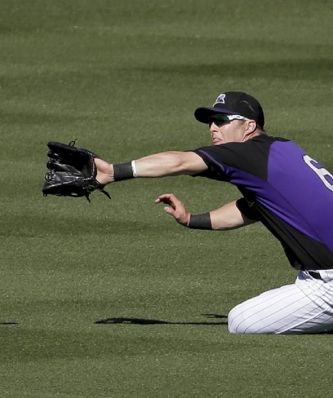 Colorado Rockies center fielder Corey Dickerson catches a fly ball hit by Oakland Athletics' Sam Fuld during the sixth inning of a spring training baseball game in Scottsdale, Ariz., Saturday, March 8, 2014
