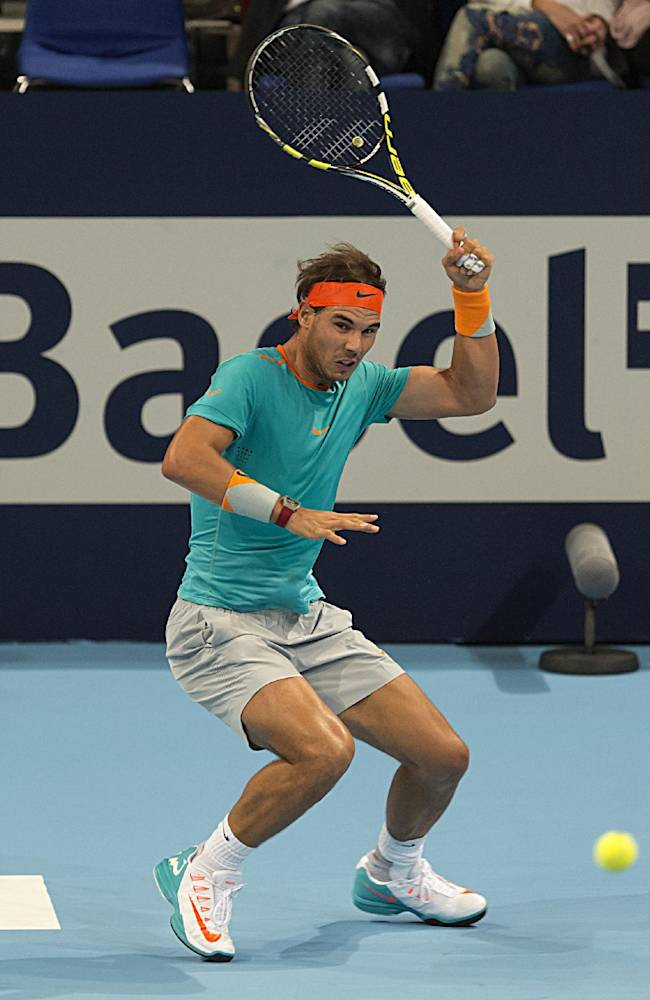 Spain's Rafael Nadal returns a ball to Italy's Simone Bolelli in the first round match during the Swiss Indoor tennis tournament at the St. Jakobshalle in Basel, Switzerland, Monday Oct. 20, 2014