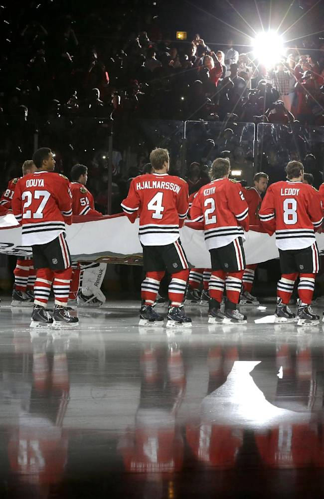 The Chicago Blackhawks carry out the Stanley Cup Championship banner during ceremonies before an NHL hockey game between the Blackhawks and the Washington Capitals Tuesday, Oct. 1, 2013, in Chicago