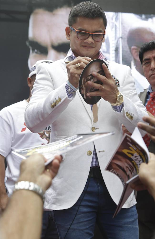 Marcos Maidana signs autographs during the outdoor portion of a news conference in Times Square, New York, Monday, July 14, 2014. Maidana will fight Floyd Mayweather for the second time in Las Vegas, Nevada on Sept. 13, 2014