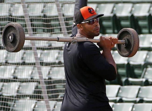 Baltimore Orioles' Nelson Cruz carries a set of wheels for a backstop off the practice field after infield practice at Ed Smith Stadium before an exhibition spring training baseball game against the Philadelphia Phillies in Sarasota, Fla., Friday, March 7, 2014