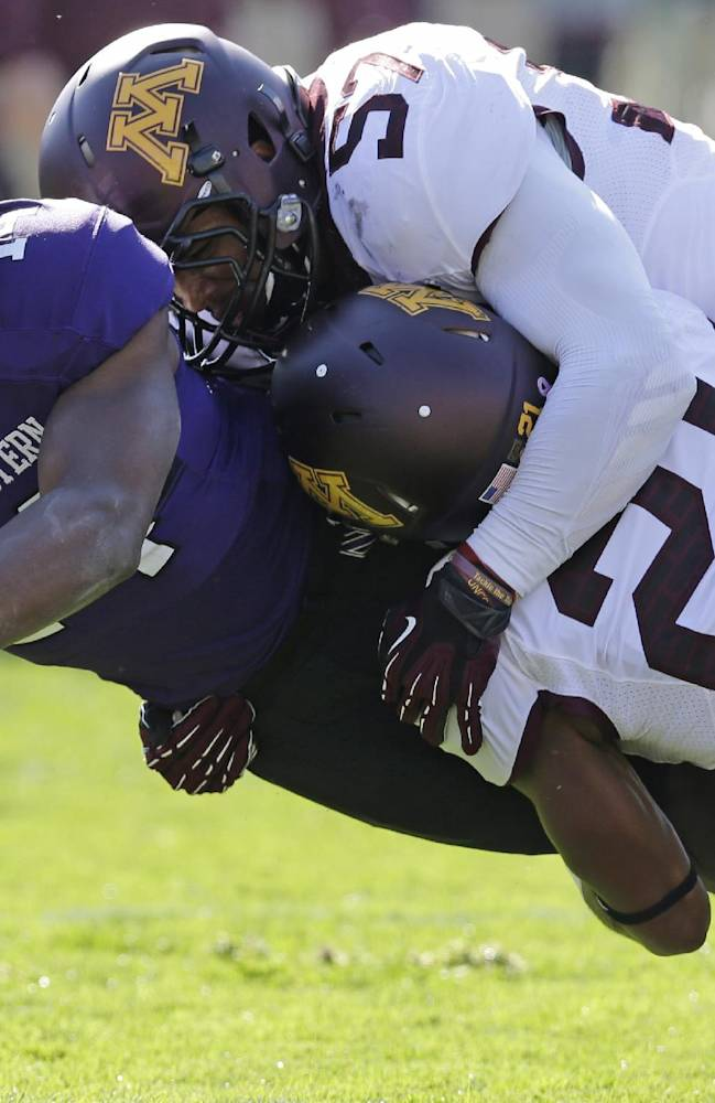Minnesota defensive back Brock Vereen (21) and linebacker Aaron Hill (57) tackle Northwestern wide receiver Christian Jones (14) during the first half of an NCAA college football game in Evanston, Ill., Saturday, Oct. 19, 2013