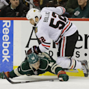 Chicago Blackhawks left wing Brandon Bollig (52) lands on Minnesota Wild defenseman Jared Spurgeon (46) as they battle for the puck during the second period of an NHL hockey game in St. Paul, Minn., Thursday, Dec. 5, 2013 The Associated Press