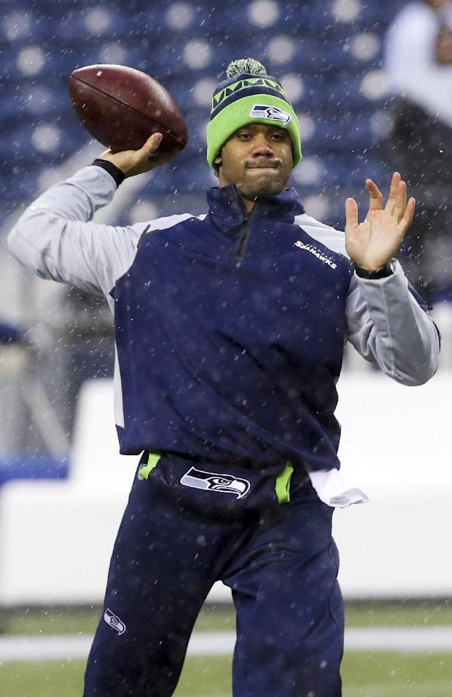 Seattle Seahawks quarterback Russell Wilson warms up before an NFC divisional playoff NFL football game against the New Orleans Saints in Seattle, Saturday, Jan. 11, 2014