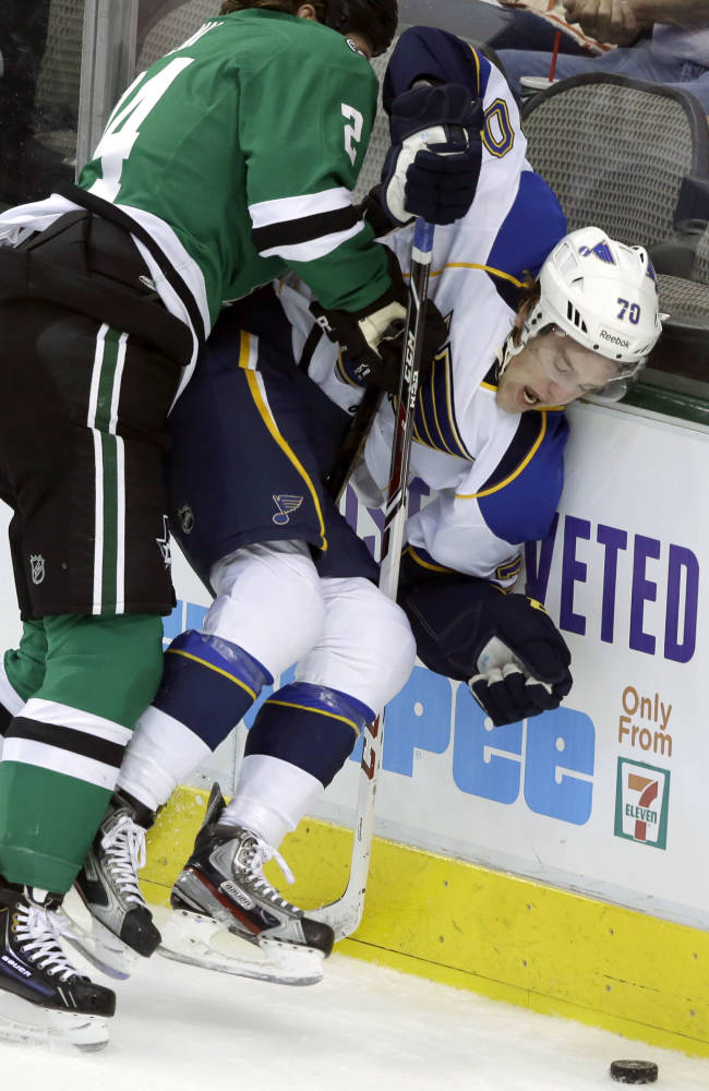 St. Louis Blues center Ryan Tesink (70) is knocked into the boards by Dallas Stars defenseman Jordie Benn (24) during the first period of an NHL pre-season hockey game Sunday, Sept. 15, 2013, in Dallas