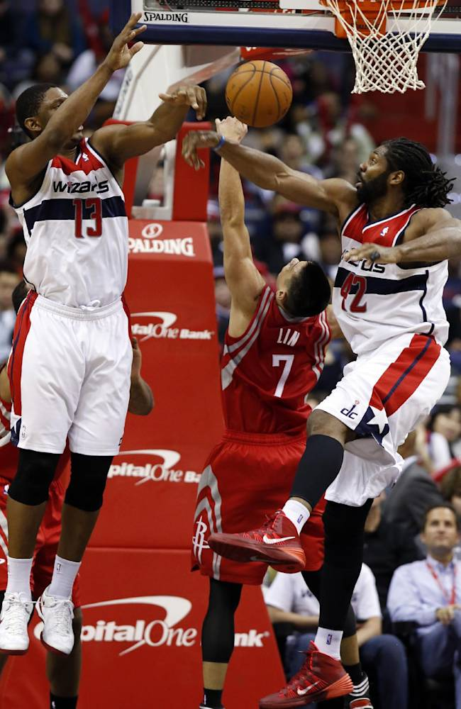 Washington Wizards center Kevin Seraphin (13), from France, and forward Nene (42), from Brazil, combine to stop a shot by Houston Rockets guard Jeremy Lin (7) during the second half of an NBA basketball game Saturday, Jan. 11, 2014, in Washington. The Rockets won 114-107