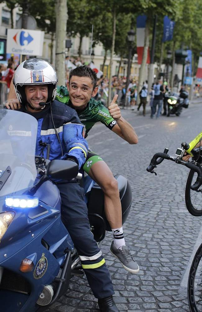 France's Perrig Quemeneur rides on the back  of the motorcycle of a French gendarme as France's Cyril Gautier, right carries his bicycle  during the team parade of the Tour de France cycling race in Paris, France, Sunday, July 27, 2014