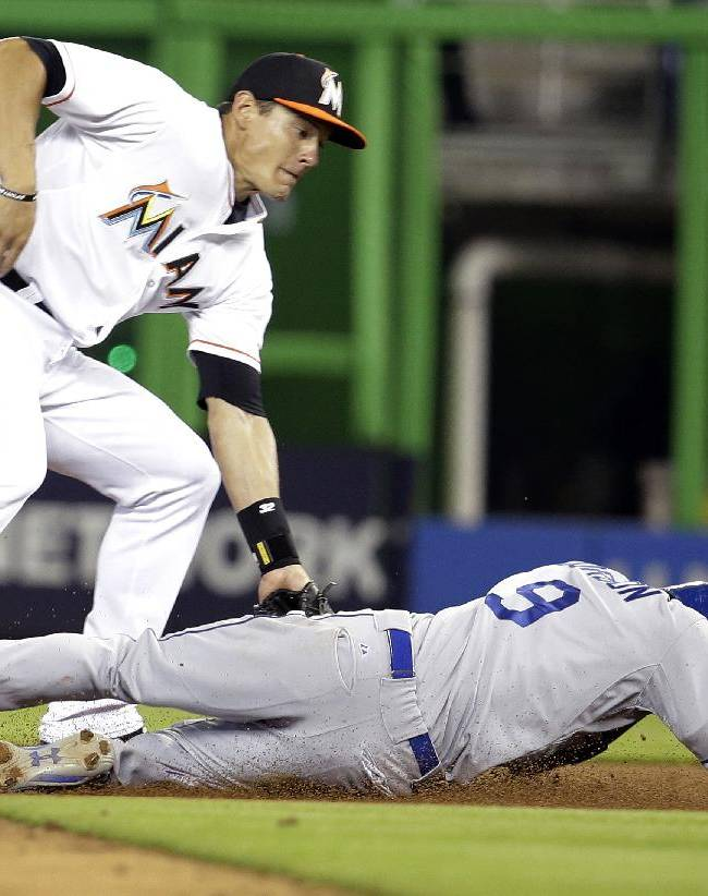 Miami Marlins second baseman Derek Dietrich, left, tags Los Angeles Dodgers' Dee Gordon in the first inning of a baseball game, Friday, May 2, 2014, in Miami. Gordon was initially ruled safe, but the call was overturned on a replay review