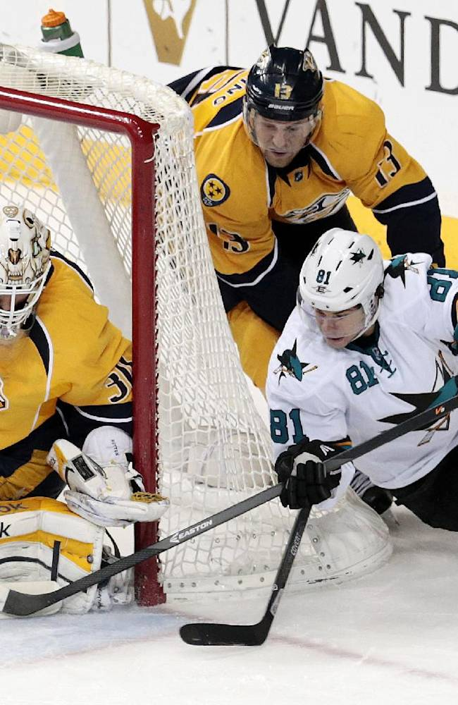 San Jose Sharks center Tyler Kennedy (81) shoots against Nashville Predators goalie Carter Hutton (30) in the second period of an NHL hockey game on Saturday, Dec. 14, 2013, in Nashville, Tenn. Predators forward Nick Spaling (13) also defends on the play