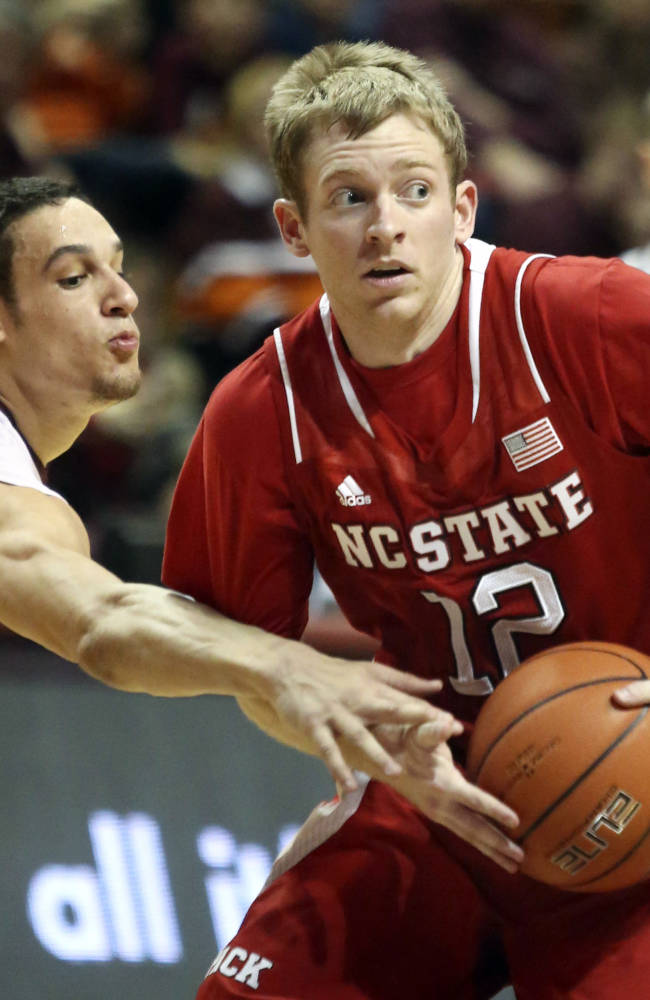 North Carolina State's Tyler Lewis (12) looks to pass as Virginia Tech's Devin Wilson defends during the first half of an NCAA college basketball in Blacksburg, Va., Saturday, Feb. 22, 2014