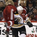 Boston Bruins' Brad Marchand (63) checks Arizona Coyotes' Oliver Ekman-Larsson, of Sweden, as he flips over Marchand during the second period of an NHL hockey game Saturday, Dec. 6, 2014, in Glendale, Ariz The Associated Press