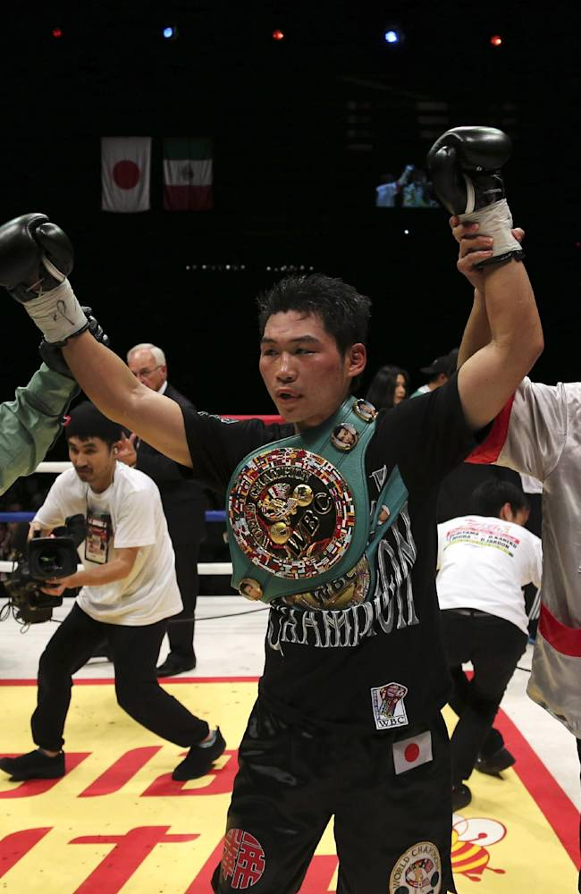 Japanese champion Takashi Miura is declared the winner by the referee, left, after defeating Mexican challenger Dante Jardon in their WBC super featherweight title bout in Tokyo Tuesday, Dec. 31, 2013. Miura defended his title by a technical knockout in the ninth round