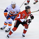 Ottawa Senators' Kyle Turris, right, and New York Islanders' Anders Lee keep their eyes on the puck during the first period of an NHL hockey game in Ottawa, Ontario, on Wednesday, April 2, 2014 The Associated Press