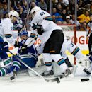 Vancouver Canucks' Ryan Kesler, left, attempts a shot on San Jose Sharks' goalie Antti Niemi, of Finland, as Brad Stuart, 7, and Justin Braun, 61, check Canucks' Daniel Sedin, third left, of Sweden, while Matt Nieto, 83, defends against Canucks' Henrik Se