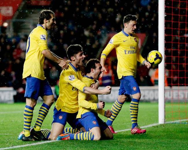 Arsenal's Santi Cazorla, third right, celebrates his goal with, from left, Mathieu Flamini, Olivier Giroud and Mesut Ozil during the English Premier League soccer match between Southampton and Arsenal at St Mary's stadium in Southampton, Tuesday, Jan. 28, 2014