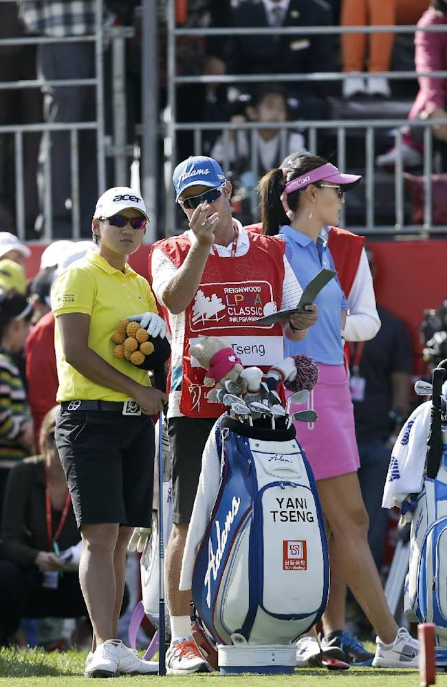 Taiwan's Yani Tseng, center left, discusses with her caddie before teeing off on the first hole during the first round of the Reignwood LPGA Classic golf tournament at Pine Valley Golf Club on the outskirts of Beijing, China, Thursday, Oct. 3, 2013